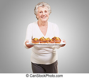 portrait of senior woman showing a chocolate muffin tray over grey background