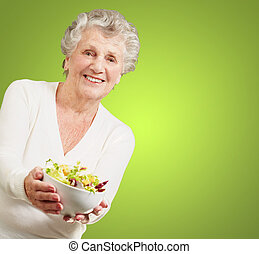portrait of senior woman showing a fresh salad over green background