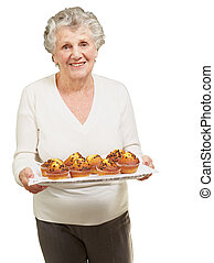 portrait of senior woman showing homemade muffins over white