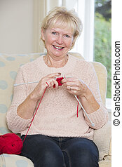 Portrait Of Senior Woman Sitting In Chair Knitting