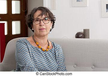 Portrait of senior woman sitting on her sofa