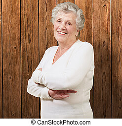 portrait of senior woman smiling against a wooden wall