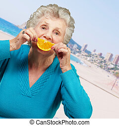 portrait of senior woman smiling and holding a orange slice in the beach