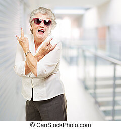 portrait of senior woman smiling and wearing sunglasses at modern office