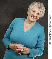portrait of senior woman standing against a grunge wall