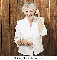 portrait of senior woman talking on mobile against a wooden wall