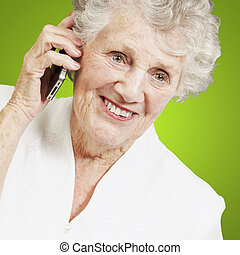 portrait of senior woman talking on mobile over green background