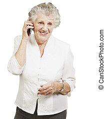 portrait of senior woman talking on mobile over white background