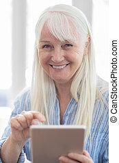 Portrait Of Senior Woman Using Digital Tablet At Home