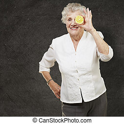 portrait of senior woman with lemon in front of her eye against a grunge wall