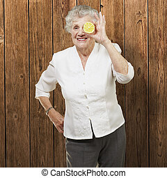 portrait of senior woman with lemon in front of her eye against a wooden wall