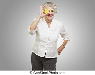 portrait of senior woman with lemon in front of her eye over gey
