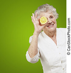 portrait of senior woman with lemon in front of her eye over green