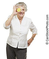 portrait of senior woman with lemon in front of her eye over white