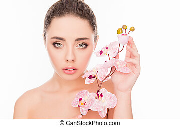 Portrait of sensetive young woman with orchid on white background