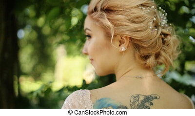 Portrait of sensual attractive tattoo bride with bouquet looking away, standing in summer forest