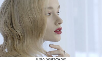 Portrait of sensual blonde woman with red lips on white background.