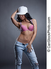 Portrait of sensual girl in cap, bra and jeans