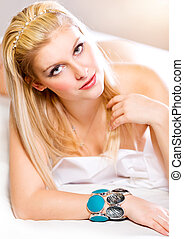 Portrait of sensual young lady with long straight blonde hair lying in bed. Retouched