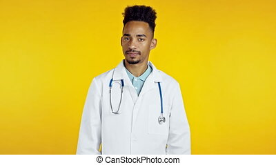 Portrait of serious african doctor in professional medical white coat showing rejecting head gesture, disapproving sign. Denying, Disagree.Doc man isolated on yellow background.High quality 4k footage