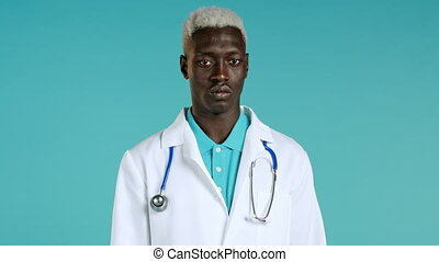Portrait of serious afro doctor in professional medical white coat showing rejecting head gesture, disapproving sign.Denying, Disagree.Black doc man isolated on blue background.High quality 4k footage