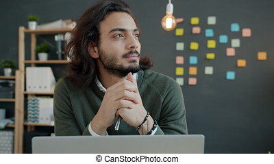 Portrait of serious Arab man office worker thinking about business sitting at computer desk