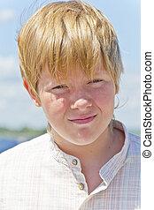 Portrait of serious boy on blue sky