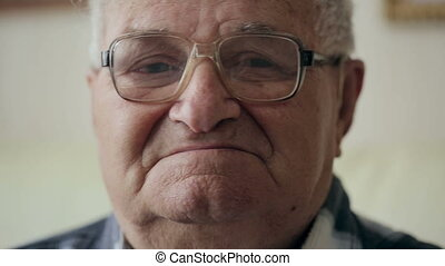 Portrait of serious caucasian old man with glasses looking at camera.