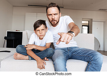 Portrait of serious concentrated man 30s and boy 8-10 pointing finger at you, while sitting on sofa in apartment