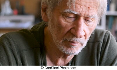 Portrait of serious concerned elderly man looking at the camera in his home dolly shot
