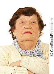 Portrait of serious elderly woman standing with arms folded...