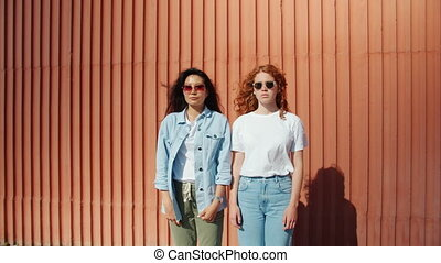 Portrait of serious girls standing outdoors in sunglasses ...