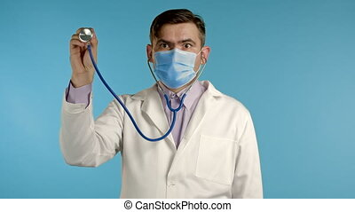 Portrait of serious handsome man in professional medical white coat using stethoscope isolated on blue studio background. Man points his instrument at camera as if he is listening to ill patient