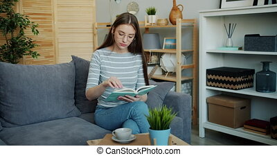Portrait of serious lady reading book on sofa in apartment...
