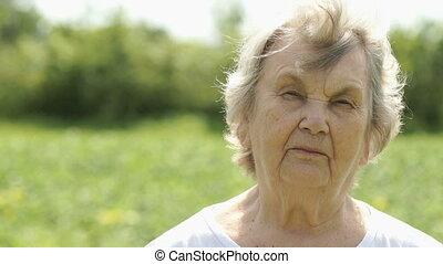 Portrait of serious mature elderly woman outdoors
