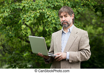 Portrait of serious middle-aged businessman holding notebook and looking at camera, outdoors