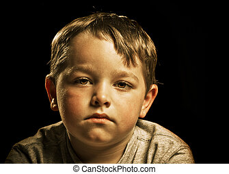 Portrait of serious, sad, angry or depressed child isolated on black