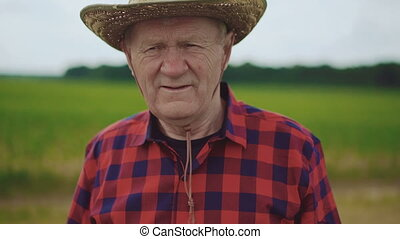 Portrait of serious senior farmer on the blurred field's background 4K