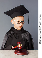 Portrait of serious smart child in graduation cap playing in judge.