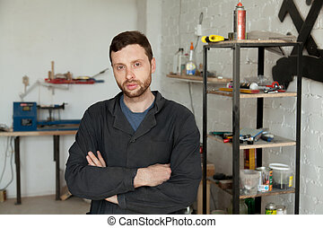 Portrait of serious young handyman standing in own workshop inte