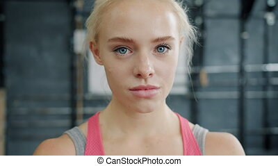 Portrait of serious young sportswoman in sports clothing looking at camera in gym standing alone. Healthy active lifestyle, people and emotions concept.