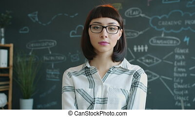 Portrait of serious young woman wearing glasses and modern clothing standing in office with chalkboard in background. People and workspace concept.