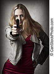 Portrait of dangerous sexy blond woman with hand gun