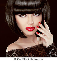 Portrait of Sexy brunette woman with short black hair, red lips, manicured polish nails. Makeup. Hairstyle. Isolated on dark background