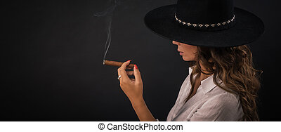 Portrait of sexy elegant lady with hat smoking cigar