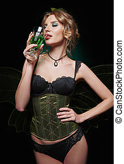 Portrait of sexy gorgeous green fairy. Seductive young girl drinking pure absinthe
