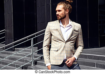 portrait of sexy handsome fashion male model man dressed in elegant beige checkered suit posing near dark blue wall in the street background
