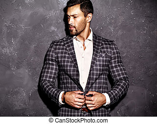 portrait of sexy handsome fashion male model man dressed in elegant suit posing near gray wall