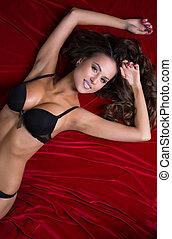 Portrait of sexy lingerie model on satin bedsheet