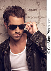 Portrait of sexy man in sun glasses. Holding on side of the glasses